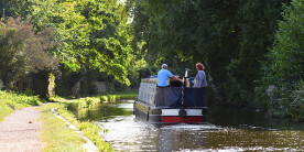 Couple driving a boat on the Coventry Canal