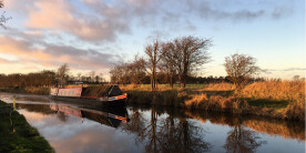 A narrowboat on the canal at sunset