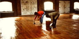 Two ladies painting a wooden floor with varnish