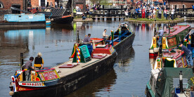 A canal boat returns to a crowd of people at Ellesmere Port