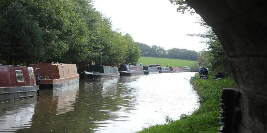 View of Middlewich Branch under bridge with moored boats and anglers on the towpath
