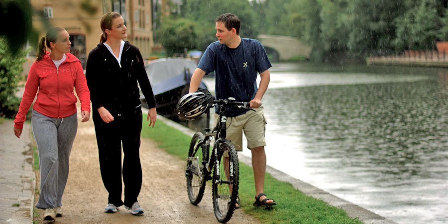 A cyclist talking to two walkers on the towpath
