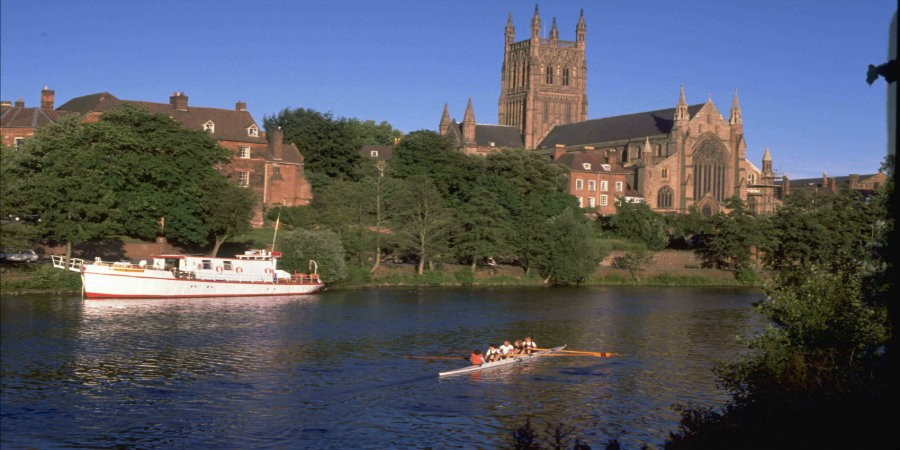 River Severn in Gloucester with rowing boat on water and cathedral in background