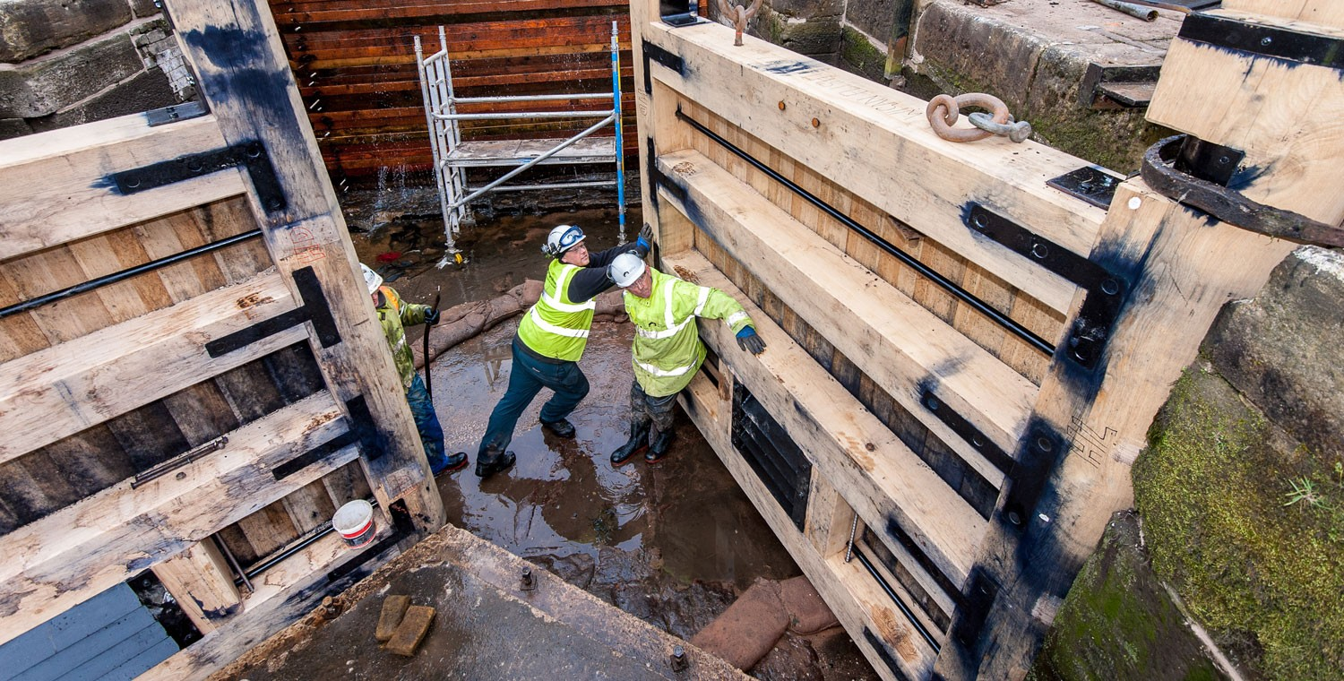 Engineers moving lock gates into place in a drained lock pound