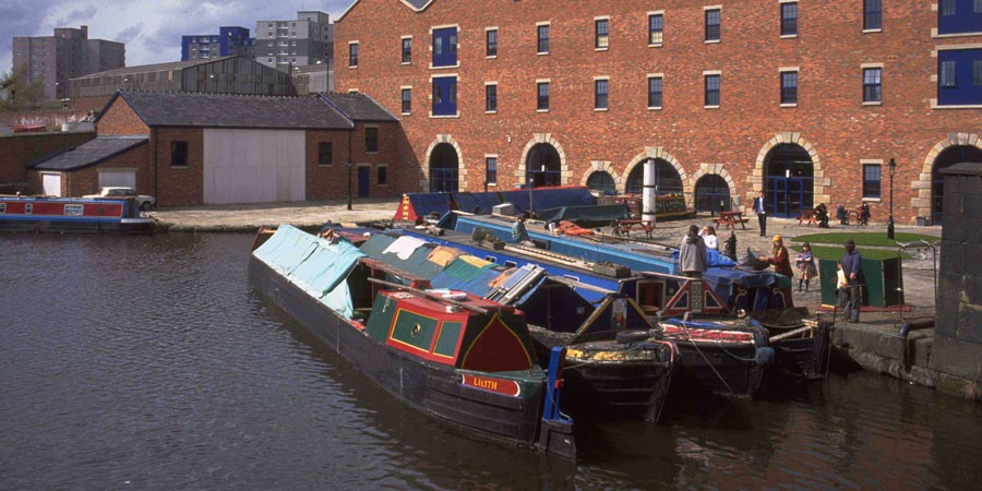Boats moored by red-brick warehouse on Ashton Canal