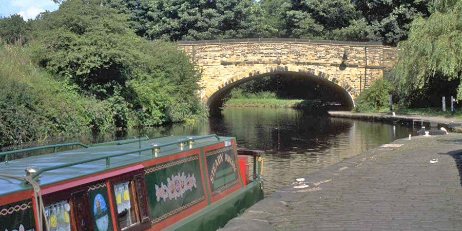 Narrowboat moored in front of bridge on Calder & Hebble Navigation