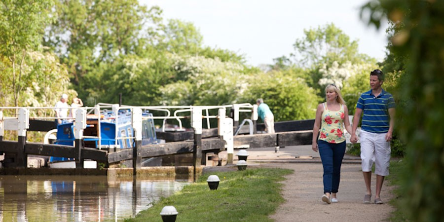 Couple walking past boat in lock on Grand Union Canal