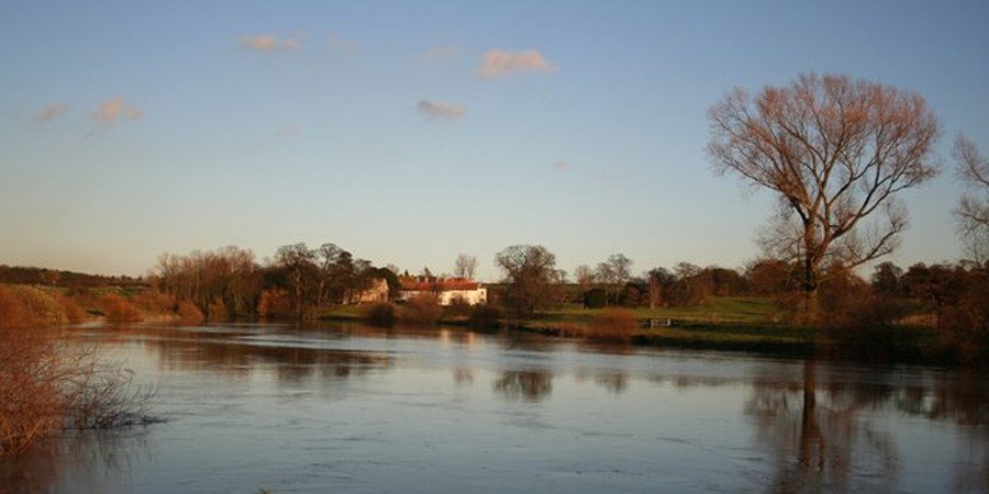 View across River Trent to white house and fields