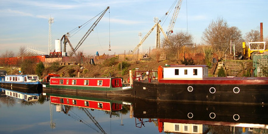 Boats moored on Navigation in industrial area with cranes in background