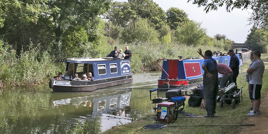 Angler waving to passengers of passing boat on Slough Arm