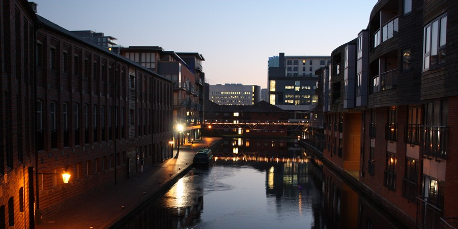 Nightime view of canal between buildings towards illuminated bridge