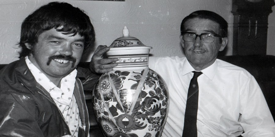 Black and white photo of Ian Heaps with his father Jim holding a trophy