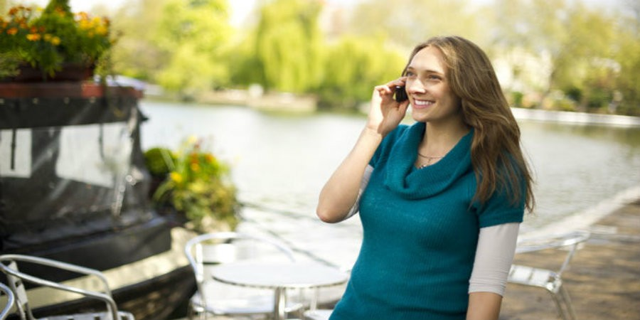 Employee stood by boat on towpath using mobile phone