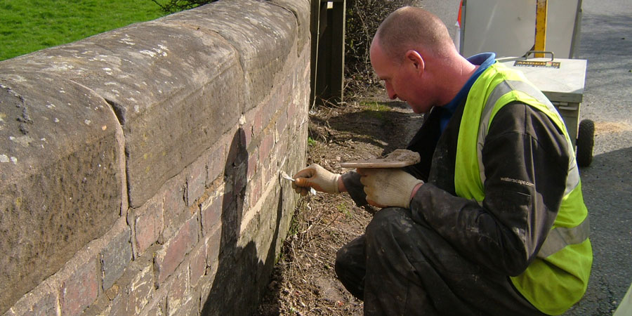 Employee repointing wall