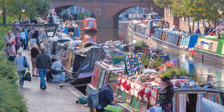Boats with bunting moored along towpath in Birmingham for floating market