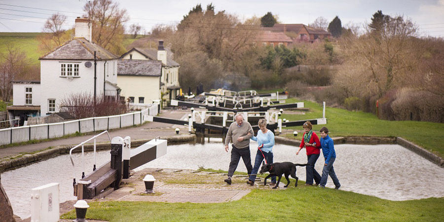 Family walking with dog by the canal