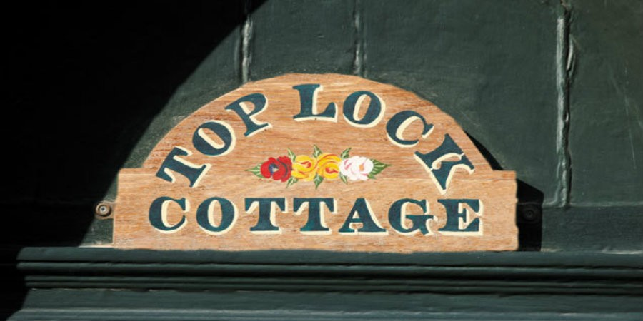 Sign for Top Lock cottage, wooden sign with green writing and roses