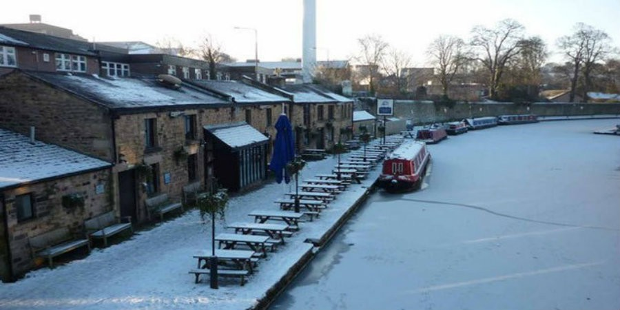 Boat moored outside canalside buildings with frozen canal