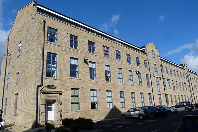 Lime Field Mill, former worsted mill, now converted to flats with cars parked in front of building