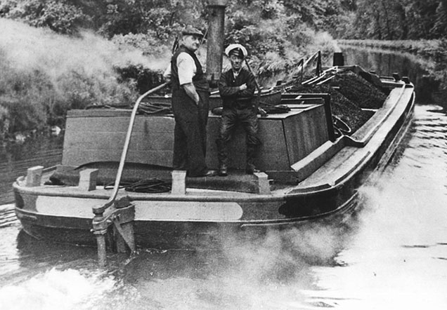 Black and white photo of steam driven short boat Skipton around 1950, carrying a cargo of domestic coal.