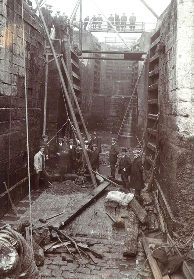 Black and white photo of workmen in bottom of lock during repairs in summer 1912