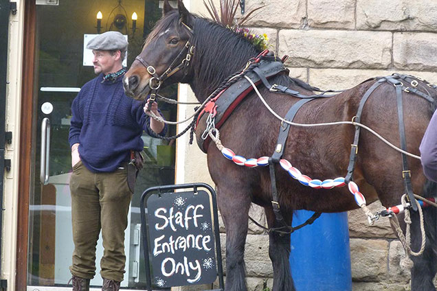 Man with boat horse outside Five Rise cafe