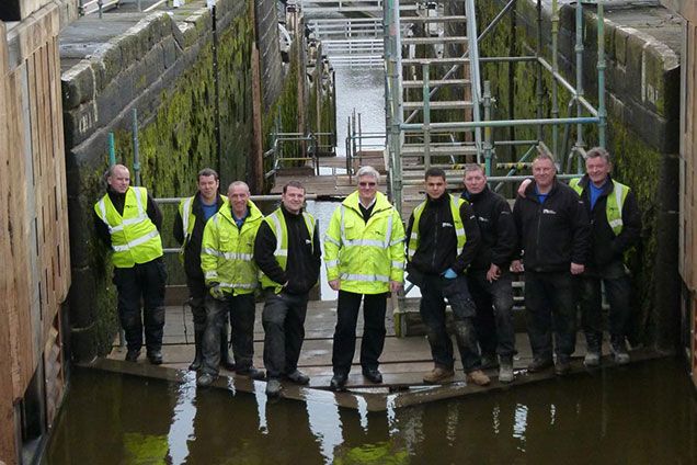 Team of carpenters in hi-vis in the bottom of Five Rise lock in 2012