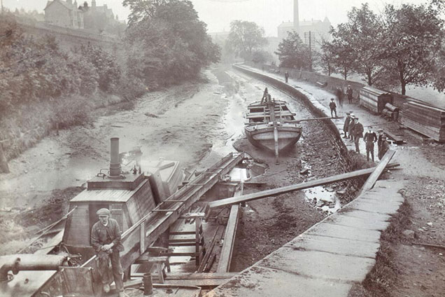 Black and white photo of workmen in a drained canal bed near Five Rise Lock