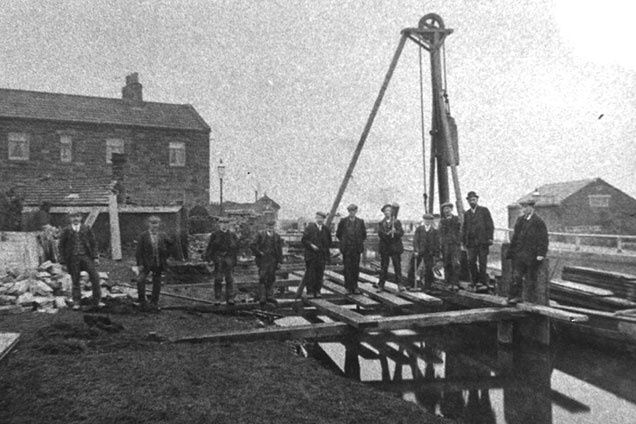 Black and white photo of workmen inserting stop planks at FIve Rise Locks