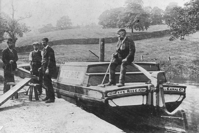 Black and white photo of canal company carpenters with maintenance boat