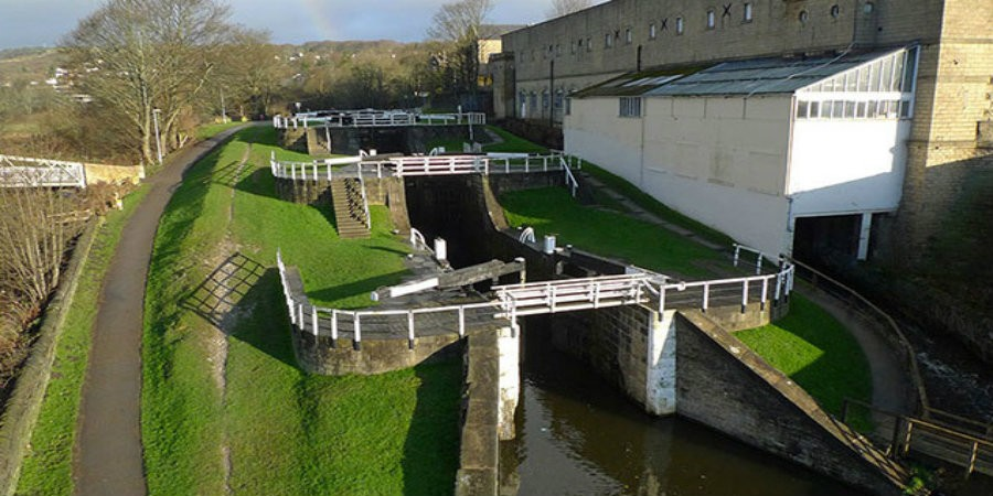 Bingley Three Rise Locks, with the white timber extension from Bowling Green Mills extending over the bywash.