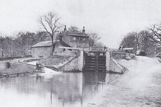 Black and white photo of Hirst Farm in foreground with two storey lock cottage to the rear, photographed around 1920.
