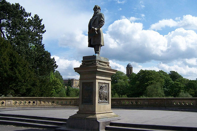 Statue of Sir Titus Salt on top of the Half Moon Pavilion in Roberts Park decorated with an alpaca and angora goat round the base.