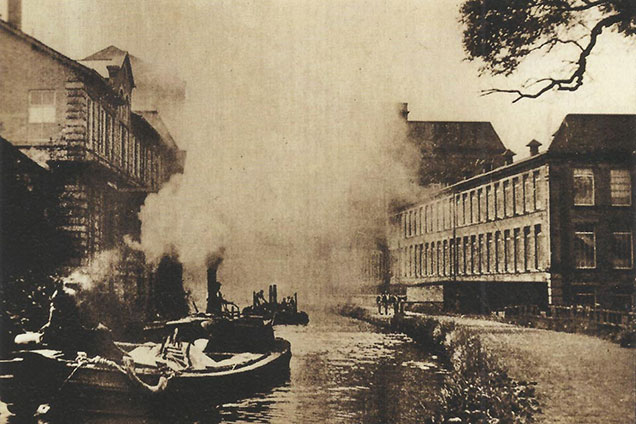 Steam powered boats coming into Saltaire from Shipley in 1936, filling the canyon with smoke. Salt's Mill is on the left, New Mill is on the right.