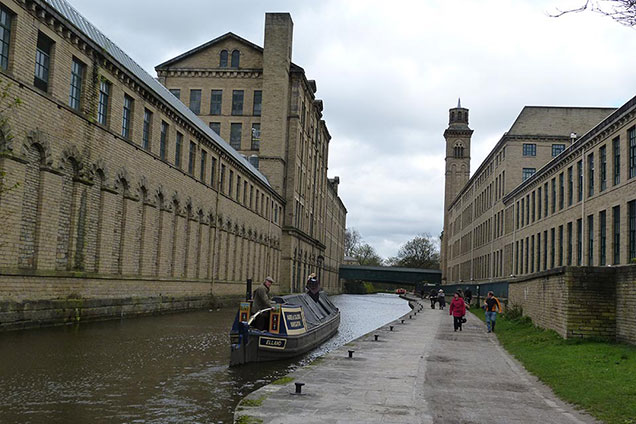 Coming from Shipley with Salt's Mill on the left and New Mill on the right with its Italian style chimney. Raised footbridge connecting the mills in the background.