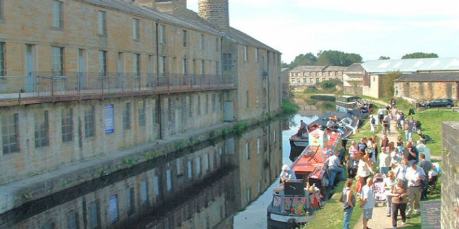Leeds & Liverpool Canal passing old warehouses, with moored boats and people on towpath in Burnley
