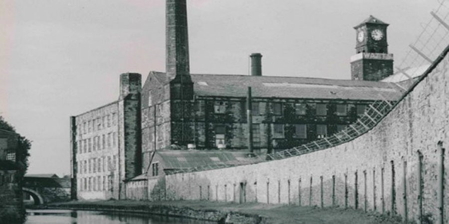 Black and water photo of clock tower mill with waterway passing in front