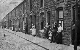 Black and white photo of people stood in the doorways of small terrace houses