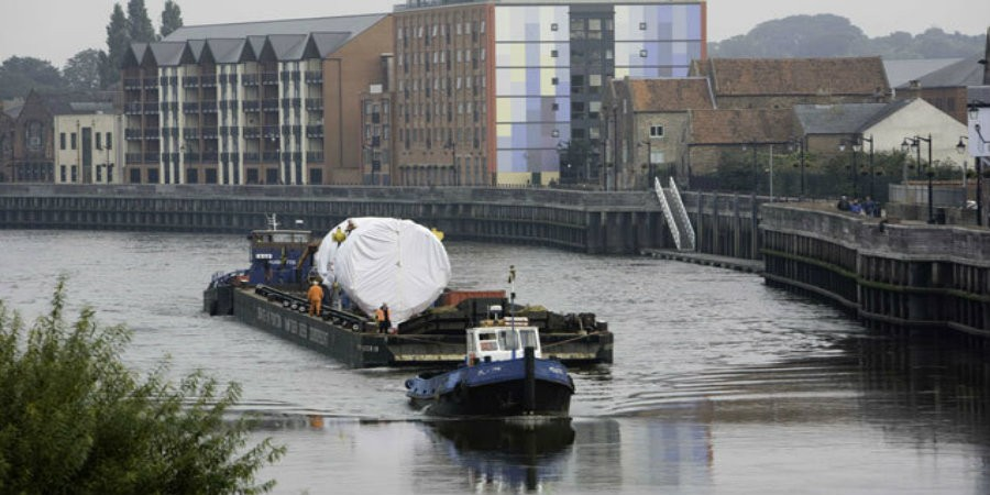 Tug pulling barge with large freight on River Trent