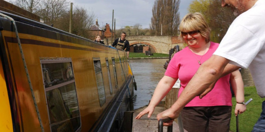 Couple working lock for narrowboat at Stoke Bruerne
