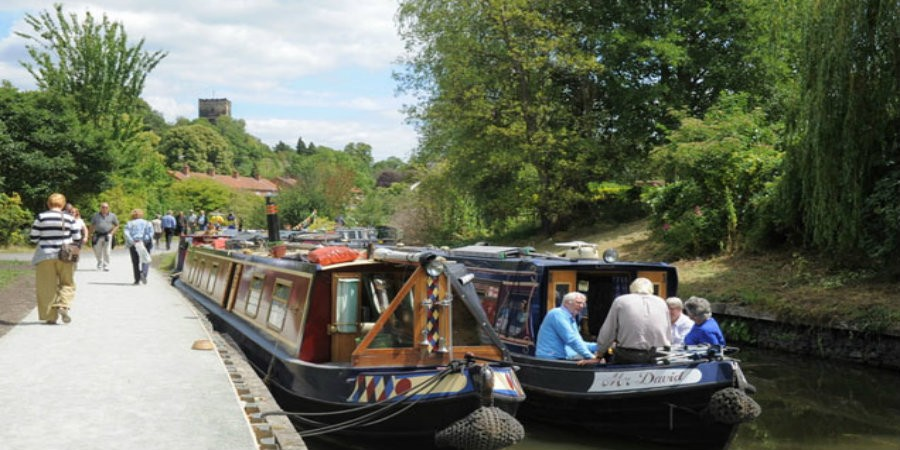 Group sat on moored narrowboat in Vines Park with people walking by on towpath
