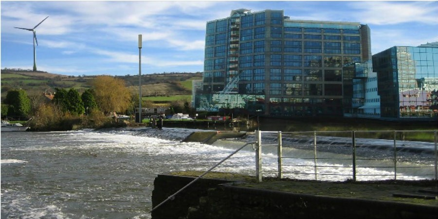 Factory with weir in foreground and wind turbine in the background