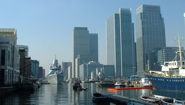 Variety of boats moored in front of buildings in London Docklands