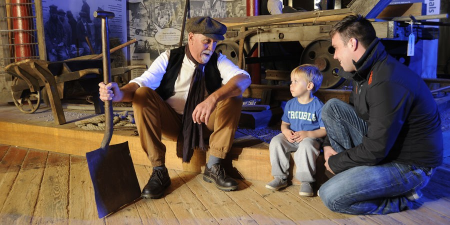 A young boy and his dad talking to a costumed character at the Gloucester Waterways Museum