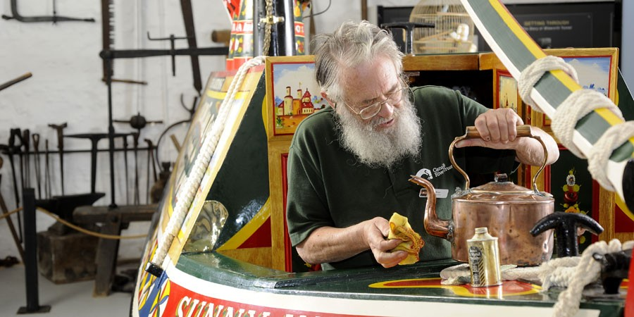 A man polishing a kettle at The Canal Museum