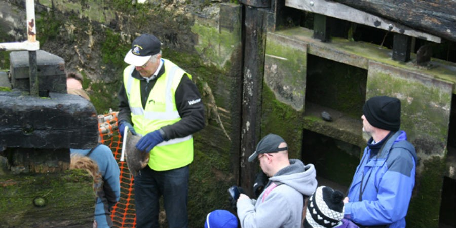 A volunteer at the bottom of Lock 66 GUC holding WW2 helmet