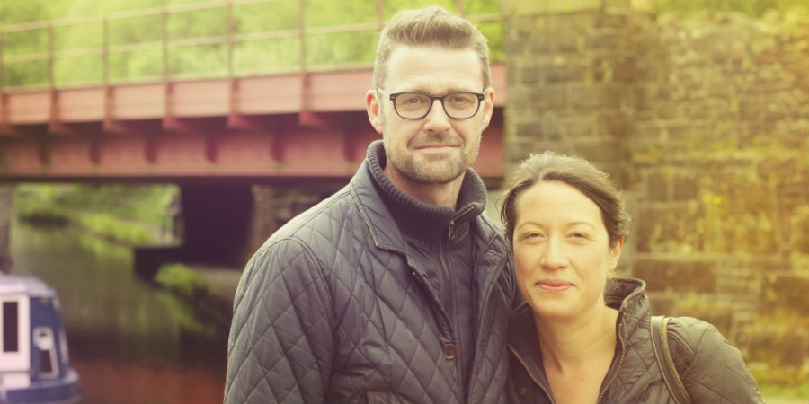 couple under a bridge by the canal