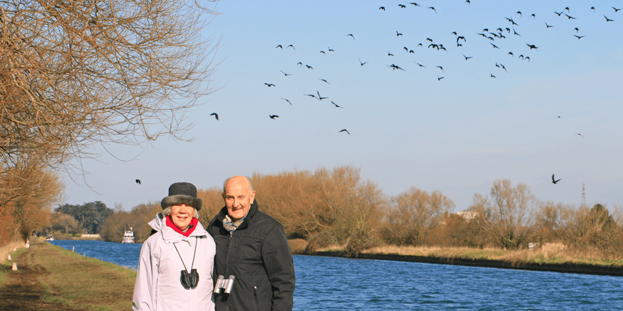Couple by the canal with birds behind them