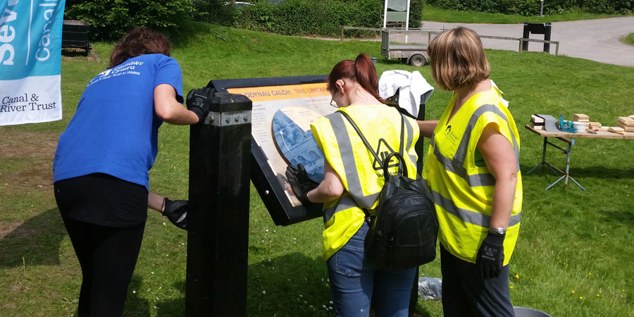Volunteers cleaning Canal & River Trust signs