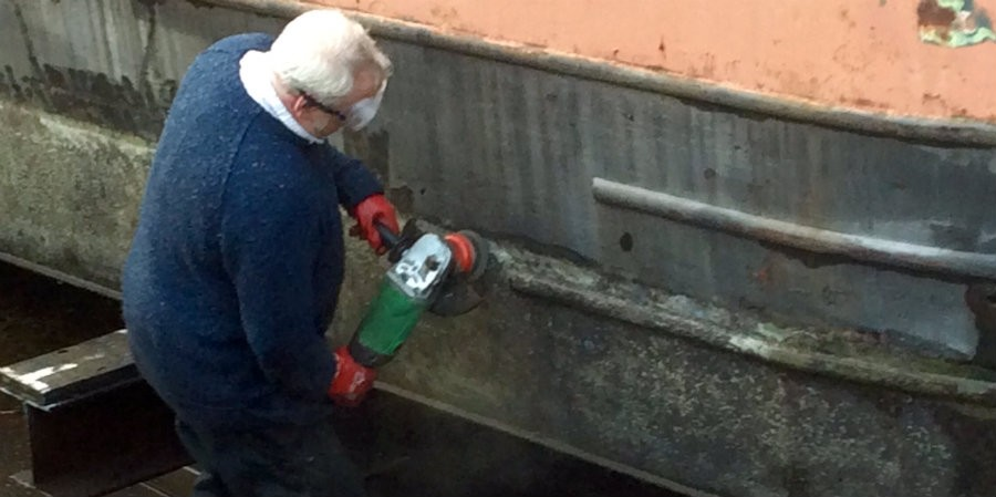 Removing loose paint from the hull with an angle grinder